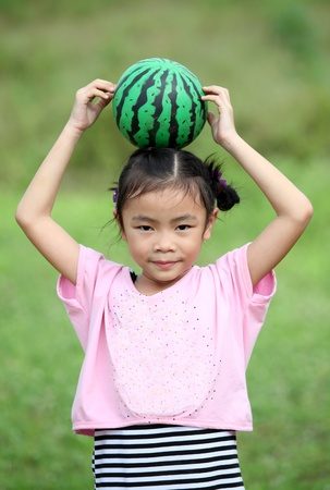 Beautiful child with Watermelon in spring field photo