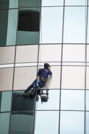 climbing cable:  worker cleaning high tower with green glass Stock Photo