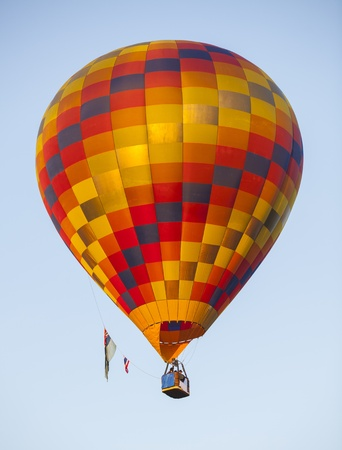 A red hot air balloon rises above the treetops during Colorado photo