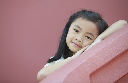 asien: young girl relax on the step with ping background. Stock Photo