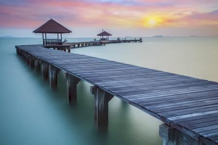 puente: Puente boscoso en el puerto entre el amanecer.