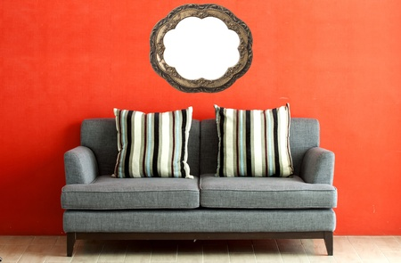 bright colors: gray sofa put on red stucco background  Stock Photo