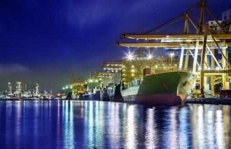 コンテナー貨物の貨物船造船所でクレーン橋ロジスティック インポートエクスポートの背景の夕暮れ時に作業に 写真素材