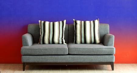 gray sofa put on red stucco background  photo