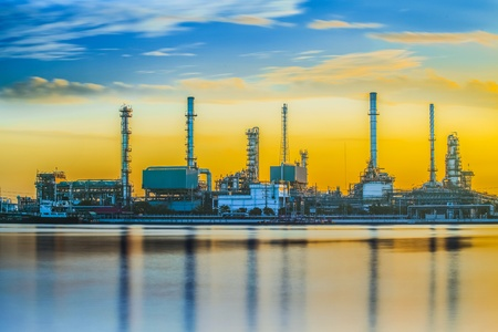 Refinery industrial plant with river and sunset