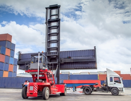 dockyard: forklift handling the container box load to big truck. Stock Photo
