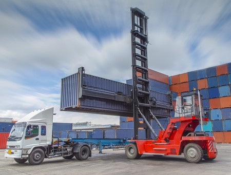 Crane lifter handling container box loading to truck photo