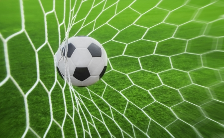 soccer ball in goal with green background photo