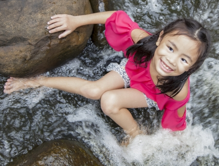 aisa: Asian girl sitting near the waterfall