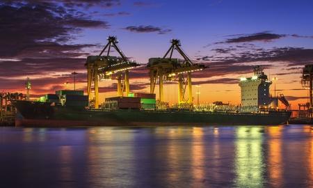 Container Cargo vrachtschip met het werken kraan brug in scheepswerf in de schemering voor Logistieke Import Export achtergrond