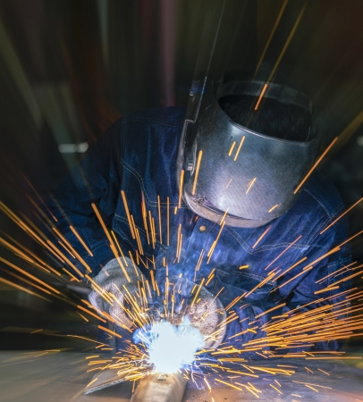 automobile industry: Worker welding the steel part by manual Stock Photo