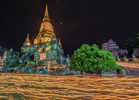 sukhothai: Buddhist and candle festival, the  people walk with lighted candles in hand around a temple  Editorial