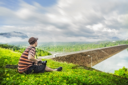 Photographer relax at Crest of the Ratchaprapa dam in Surat Thani, Thailand photo