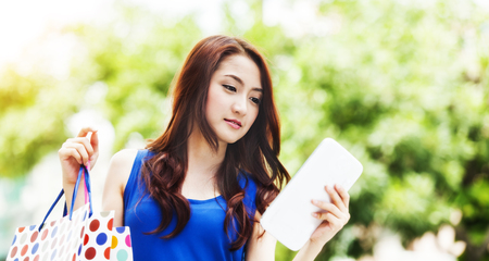 Beautiful young asian woman using tablet computer between shopping photo