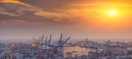 import: Container Cargo freight ship with working crane bridge in shipyard at dusk for Logistic Import Export background