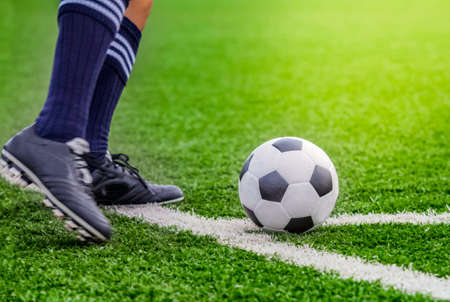 soccer boots: Kick off soccer ball with his feet on the football field