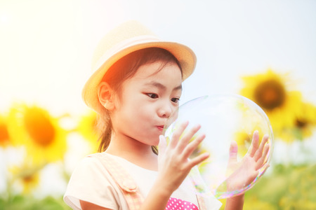 Asian little girl is blowing a soap bubbles in sunflower garden, Outdoor Portrait photo