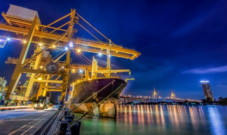 Landscape of Container Cargo freight ship with working crane bridge in shipyard at dusk for Logistic Import Export background
