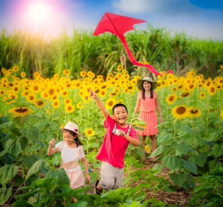 Family mother and son in summer playing with kite with sun flower gardent