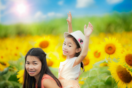 Happy family with beautiful sunflowers in spring field photo