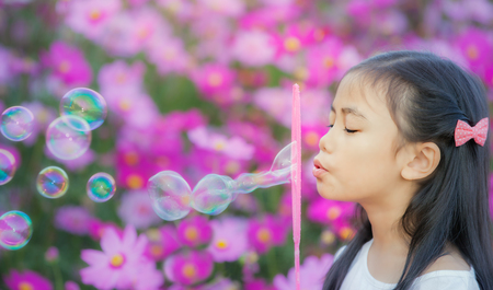 Asian little girl is blowing a soap bubbles in cosmos garden, Outdoor Portrait photo