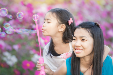 Asian little girl is blowing a soap bubbles with her mather in cosmos garden, Outdoor Portrait family photo