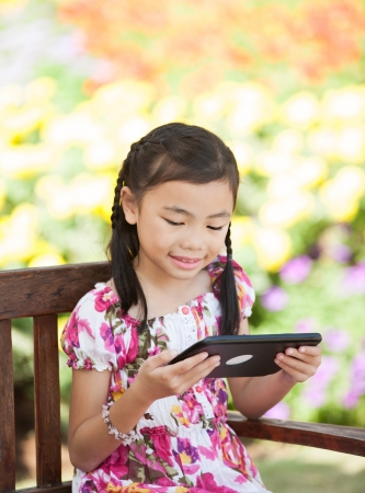 Asian young Girl play a tablet photo