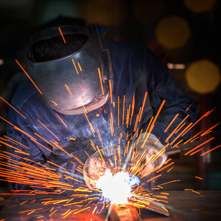 Worker welding the steel part by manual Imagens