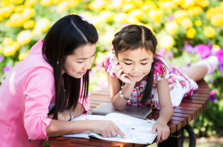 Mon and baby take a home work on the green nature and flower garden