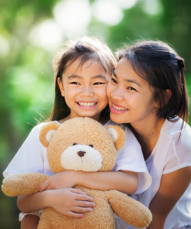 Asia little girl and her mather with doll bear in nature park photo