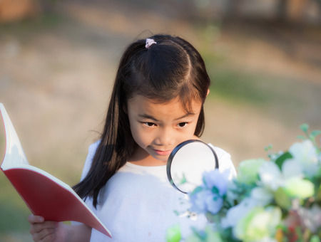 Asian girl with magnifying glass outdoors and note for flower description Standard-Bild