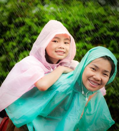 Asiatisches kleines Mädchen genießen den regen in einem Regenmantel mit ihrer Mutter angezogen