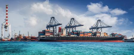 Container Cargo de marchandises de travailler pont grue de chargement dans le chantier naval au crépuscule pour Logistique Import Export fond Banque d'images