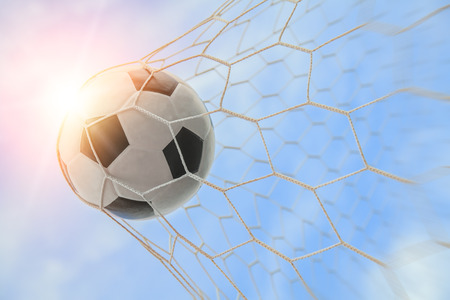 soccer ball in goal with blue sky Imagens