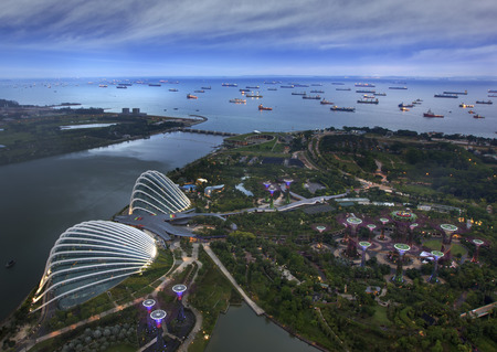 Landscape from bird view of Cargo ships entering one of the busiest ports in the world, over the Garden by the bay in Marina bay sand