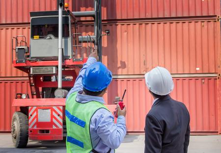 Vorarbeiter Steuerstaplerfolgeauftrag von seinem Manager für Bewegen Sie den Container-Box Lade Standard-Bild