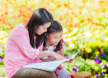 Mon and baby take a home work on the green nature. photo