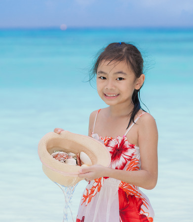 songkran: Asia tourist girl holding had and starfish and shell in tropical beach