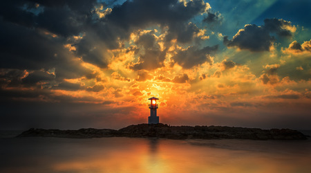 Lighthouse with light beam at sunset at Khao Lak 免版税图像