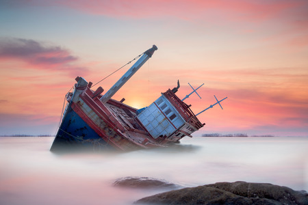 Fishing boat beached with sunset view Stock Photo