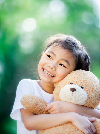 Asia little girl with doll bear in nature park photo
