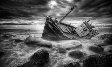 Fishing boat beached in storm in the stone beach, sea, island.