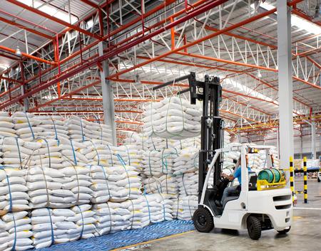 montacargas: Cargador de carretilla elevadora con el bolso grande de azúcar en almacén de distribución