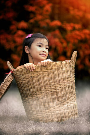 Young girl Sitting In Basket with morning Autumn photo