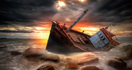 storm tide: Fishing boat beached with sunset view Stock Photo
