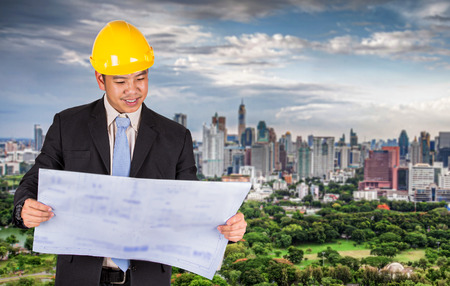 urban environment: Asian civil engineer in hardhats taking a look at the blueprint in urban environment Stock Photo