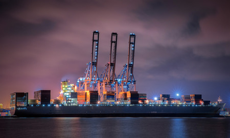 Container Cargo freight ship with working crane loading bridge in shipyard at dusk for Logistic Import Export background photo