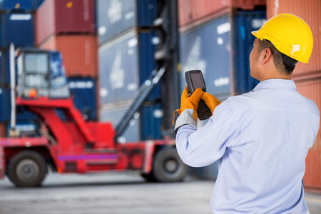 customs: foreman control forklift handling the container box load to big truck selective focust at container box.