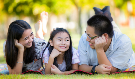 Happy asian mother, father and daughter relax in the park photo