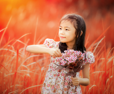 Asia little girl laughing in a meadow - happy girl in autumn background photo